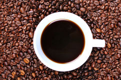 CUP OF COFFEE IN COFFEE BEANS Stock Photo