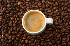 Cup of coffee and coffee beans. White cup of coffee and roasted coffee beans Royalty Free Stock Images
