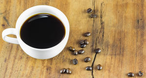 Cup of coffee and coffee beans on wood background, warm toning Stock Image