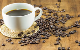 Cup of coffee and coffee beans on wood background Royalty Free Stock Photos