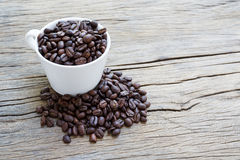 Cup coffee and coffee beans on wooden background Stock Images