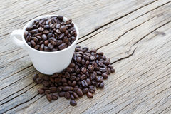 Cup coffee and coffee beans on wooden background Royalty Free Stock Photo