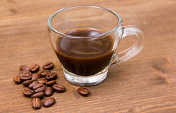 Cup of coffee and coffee beans on wooden closely Royalty Free Stock Photos