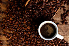 Cup of coffee with coffee beans and wooden ladle Royalty Free Stock Photos