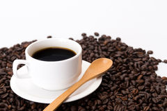 Cup of coffee on coffee beans. With wooden spoon Stock Photo