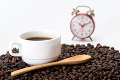 Cup of coffee on coffee beans. With wooden spoon and red alarm clock Stock Images