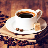 Cup of coffee with coffee beans on wooden table on brown backgro Royalty Free Stock Photo