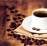 Cup of coffee with coffee beans on wooden table on brown background closeup. Cup of espresso and white saucer on brown napkin wit stock images