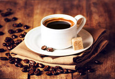 Cup of coffee with coffee beans on wooden table on brown backgro Stock Photos