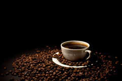 Cup of coffee on coffee grains. On a black background Stock Photography