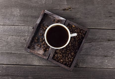 Cup of coffee and coffee grains in box on a wooden background.  Stock Photography