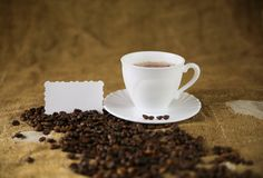 Cup of coffee with coffee grains on the old sacking background Royalty Free Stock Images