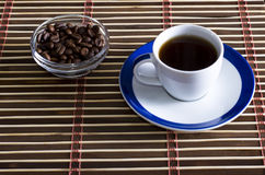 Cup of coffee with coffee grains on a saucer Royalty Free Stock Image