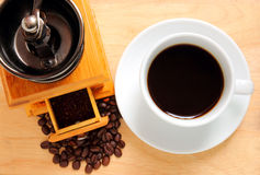 Cup of coffee with coffee grinder and beans Royalty Free Stock Photos
