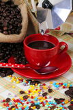 Cup of coffee with coffee maker. Coffee cup with jute sack and coffee maker on colorful background with colored sugar pearls Royalty Free Stock Image
