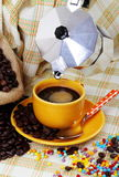 Cup of coffee with coffee maker. Coffee cup with jute sack and coffee maker on colorful background with colored sugar pearls Royalty Free Stock Photography