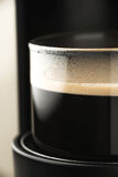 Cup of coffee in the coffee maker royalty free stock image