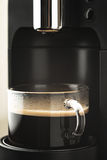 Cup of coffee in the coffee maker vertical stock image