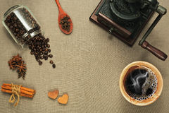 Cup of coffee, coffee mill and different spices on rude textile. Cup of coffee, jar with roasted coffee beans, vintage coffee mill and spices - cinnamon, clove royalty free stock images