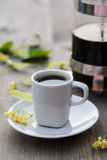 Cup of coffee, coffee pot and linden flower on the table.  royalty free stock photo