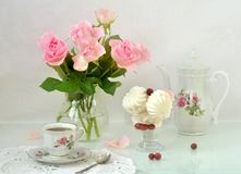 A cup of coffee, a coffee pot, a marshmallow in a glass bowl and a bouquet of pink roses on the table. Still life. Table setting. Royalty Free Stock Photo