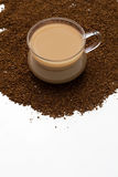 Cup of coffee and coffee powder as background. Cup of coffee and coffee powder on the table Royalty Free Stock Images