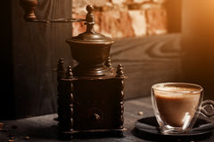 Cup of coffee in coffee shop vintage color. Coffee grinder and Brown cane sugar on wooden table with flare blurred Royalty Free Stock Images