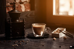 Cup of coffee in coffee shop vintage color. Coffee grinder and Brown cane sugar on wooden table with flare blurred Stock Image