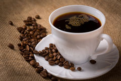 Cup of coffee with coffeebeans on linen material. Stock Photo