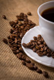 Cup of coffee with coffeebeans on linen material. Royalty Free Stock Images
