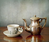 A cup of coffee and a coffepot on a wooden table Stock Image