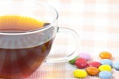 Cup of coffee and colorful chocolate. This is a picture of colorful chocolate and coffee cup placed on the table cloth Royalty Free Stock Photos
