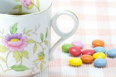 Cup of coffee and colorful chocolate. This is a picture of colorful chocolate and coffee cup placed on the table cloth Stock Photography
