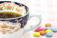 Cup of coffee and colorful chocolate. This is a picture of colorful chocolate and coffee cup placed on the table cloth Stock Image
