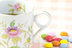 Cup of coffee and colorful chocolate. This is a picture of colorful chocolate and coffee cup placed on the table cloth Royalty Free Stock Photo