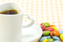 Cup of coffee and colorful chocolate. This is a picture of colorful chocolate and coffee cup placed on the table cloth Royalty Free Stock Image