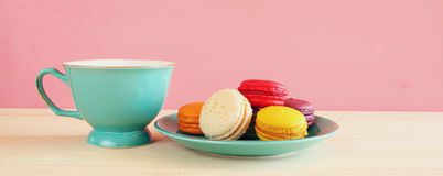 Cup of coffee and colorful macaron on wooden table Stock Photo