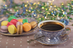 Cup of coffee with colorfull macaroons on a table. With xmas lights stock image
