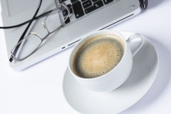 Cup of coffee with computer and glasses Royalty Free Stock Photo