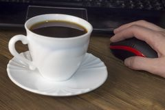A cup of coffee computer, mouse, hand, wooden background mouse stock photo