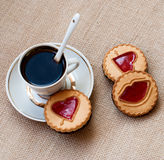 Cup of coffee and a cookie with a heart of marmalade Stock Images