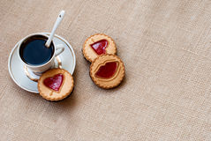 Cup of coffee and a cookie with a heart of marmalade Royalty Free Stock Photo