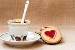Cup of coffee and a cookie with a heart of marmalade Stock Photos