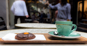 Cup of coffee and a cookie outdoors. Cup of coffee and a cookie on a table placed on the street, urban background Royalty Free Stock Image