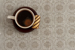 Cup of coffee and cookie on plate against monochromic tablecloth with copy space Royalty Free Stock Photo