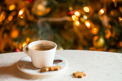 Cup of coffee with cookies. Bright Christmas lights in background royalty free stock photography