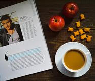 Cup of coffee, cookies and apples. Behind reading the magazine Stock Images