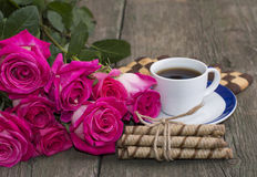 Cup of coffee, cookies and bouquet of scarlet red roses Royalty Free Stock Image