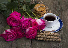 Cup of coffee, cookies and bouquet of scarlet roses Royalty Free Stock Photos