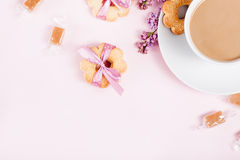 Cup of coffee with cookies, candies and lilac flowers on pink ba Stock Photos